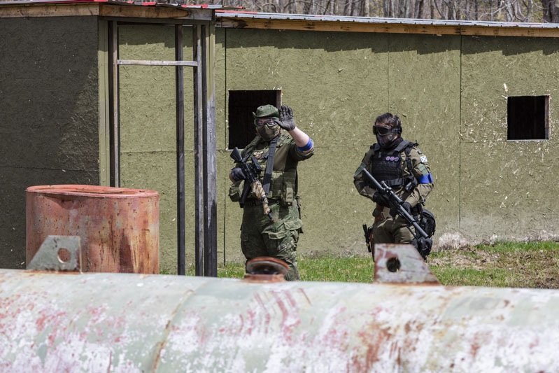 players waving at camera during paintball game