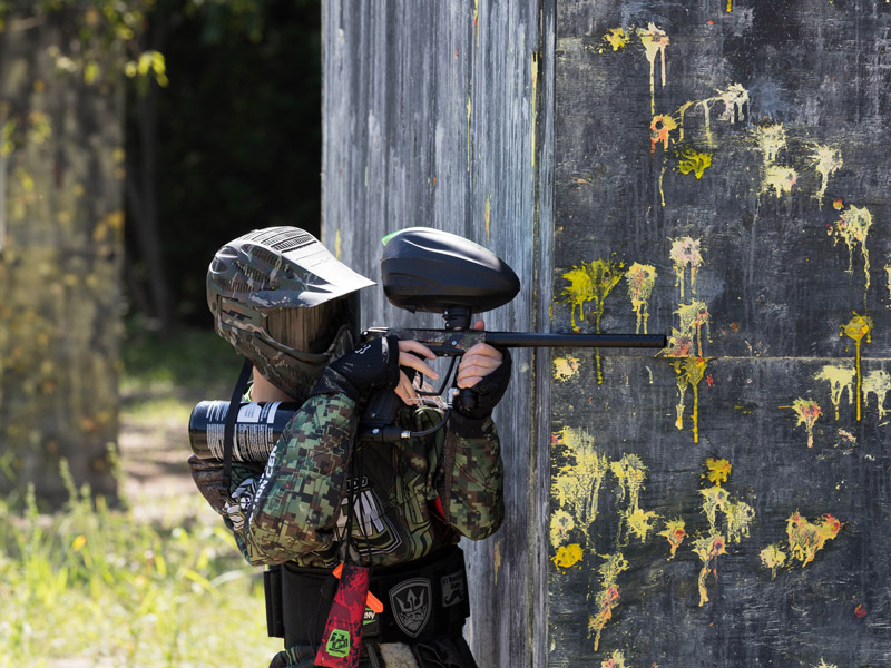 boy playing paintball with his friends