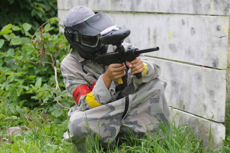 boy crouching behind bunker to shoot paintball