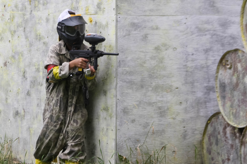 boy hiding behind wall at paintball range