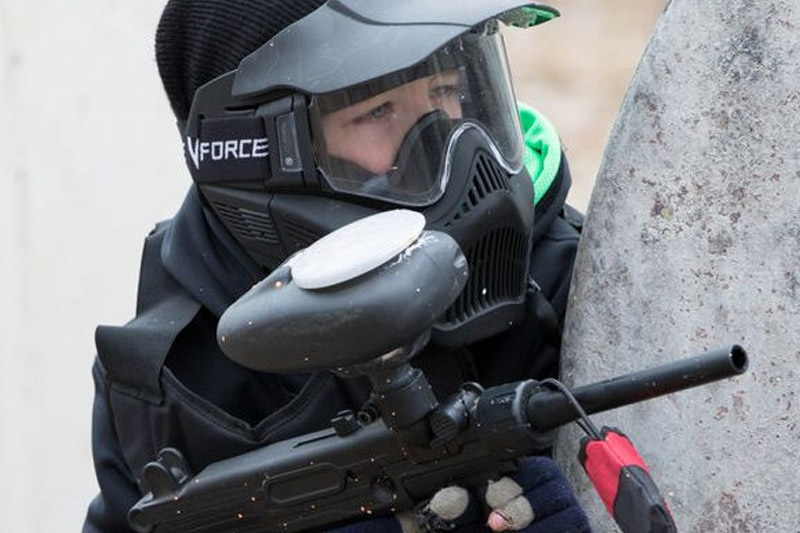 close up of boy shooting paintball gun behind bunker