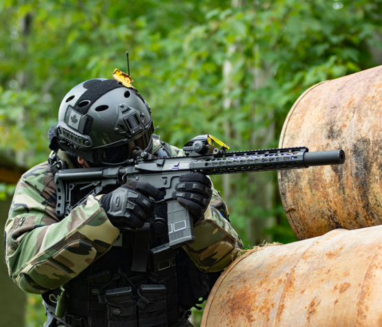 photo of paintball player in Ottawa hiding behind barrels